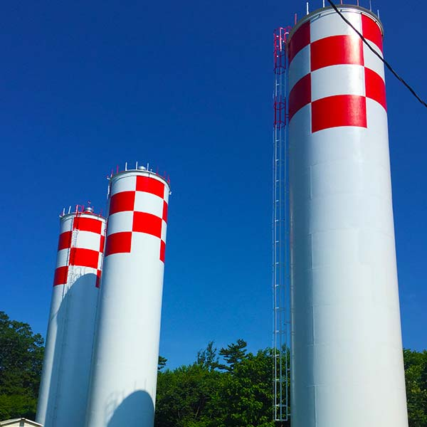Three checkered red and white water silos rise up into the blue sky.