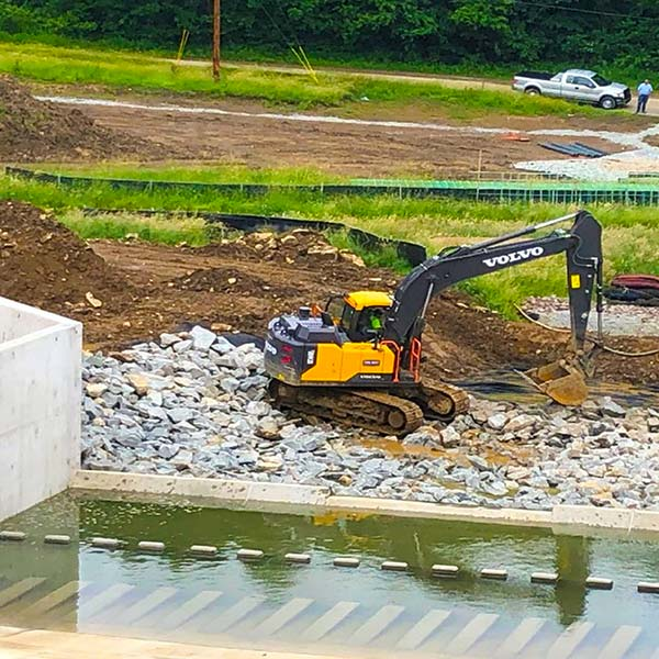 An excavator moves rocks near a dam.